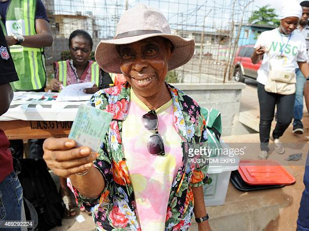 A voter shows her polling card after completing formalities using a biometric registration system at a polling station in the Apapa district of Lagos...