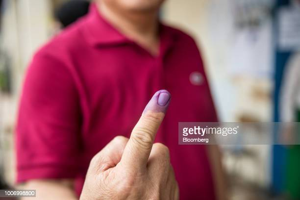 A voter shows his finger marked with ink after casting his ballot for the general election at a polling station in Phnom Penh Cambodia on Sunday July...