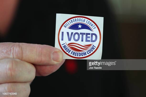 A voter shows off his 'I Voted' sticker after voting at the Jimmie B Keel regional library polling station on October 22 2018 in Tampa Florida...