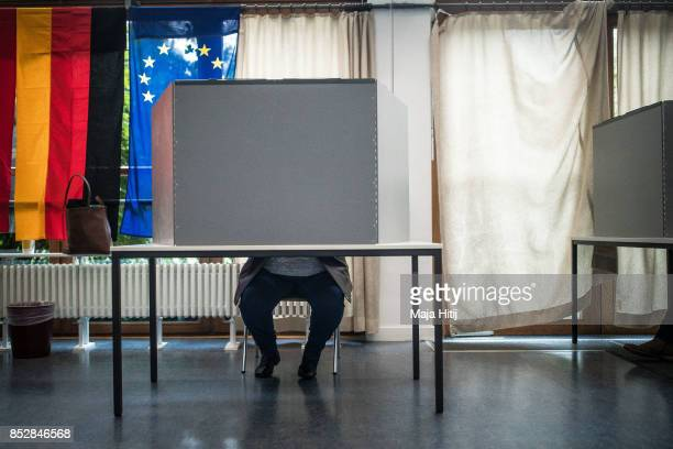 Voter sits behind voting booth as he fills her election ballot at a polling station during German federal elections on September 24 2017 in Berlin...