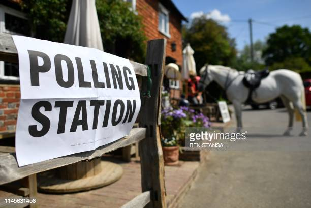 A voter sits with her horse after riding to a polling station set up in a pub to vote in the European Parliament elections near Tonbridge south east...
