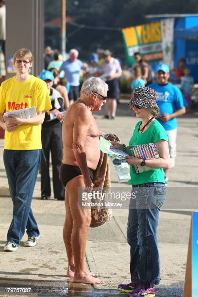 A voter speaks to party supporters outside the Clovelly Surf Life Saving Club in the electorate of KingsfordSmith on election day on September 7 2013...