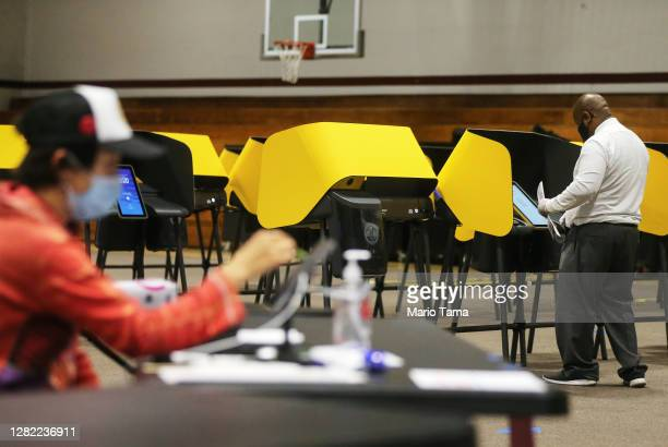 Voter stands at the voting booth as en election worker sits at a Vote Center located at Compton College on the first weekend of early in-person...