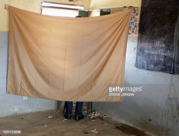 A voter stands behind a screen as he casts his vote at a polling station in Libreville on October 27 in the second round of legislative elections...