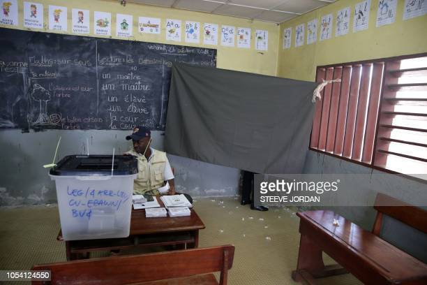 TOPSHOT A voter stands behind a screen as he casts his vote while an official looks on at a polling station in Libreville on October 27 in the second...