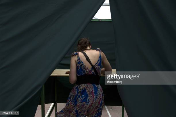A voter stands in a booth to cast a ballot at a polling station during the second round presidential general elections in Santiago Chile on Sunday...