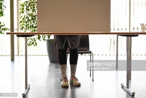Voter stands in a voting booth at a polling station in Ludwigsburg, southern Germany, to fill out the ballot paper for state elections in the...