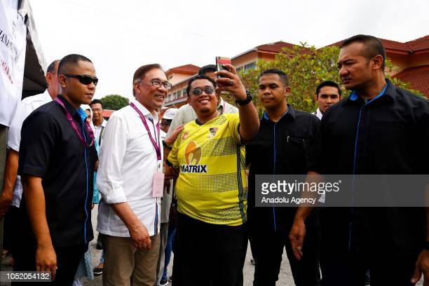A voter takes photo with Anwar Ibrahim leader of the Pakatan Harapan Coalition after casting his vote at a polling station during byelection in Port...