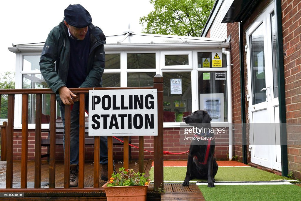 A voter ties the lead of Guia, a Labrador rescued from Ecuador, to a fence post outside a polling station in Stalybridge on June 8, 2017 in Greater Manchester, United Kingdom. Polling stations have opened as the nation votes to decide the next UK government in a general election