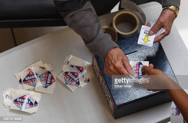 A voter turns in an activation card and receives an I Voted sticker on the first day of early voting at the Meadows Mall on October 20 2018 in Las...