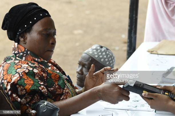 A voter uses a machine to print her thumbprint during the Osun State gubernatorial election in Ede in the Osun State in southwest Nigeria on...