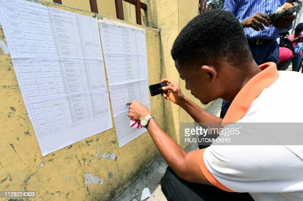 A voter uses a smartphone to photograph his details on a voters' list displayed at the Independent National Electoral Commission central office in...