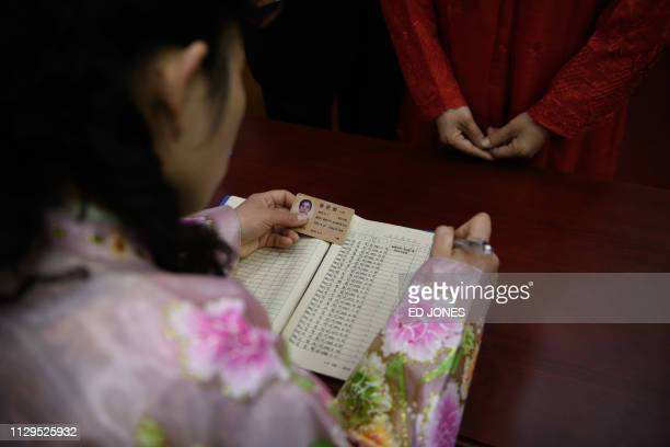 A voter uses an ID card to register to cast their ballot at the '326 Pyongyang Cable Factory' during voting for the Supreme People's Assembly...