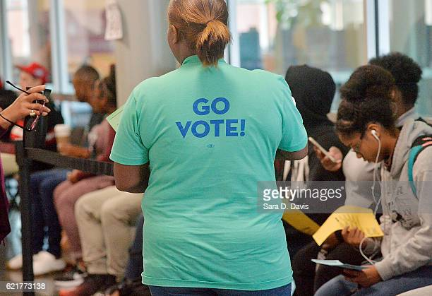 A voter waits in a long line caused by a countywide clinch in the Board of Elections' computer system on November 8 2016 in Durham North Carolina The...