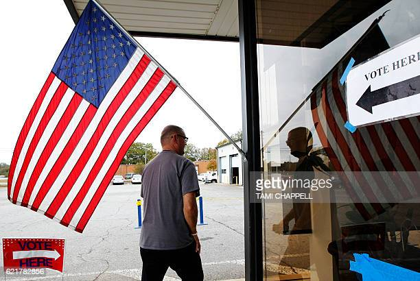 A voter walks past a US flag as he heads in to vote in the US presidential election at the AthensClarke County Fleet building in Athens Georgia on...