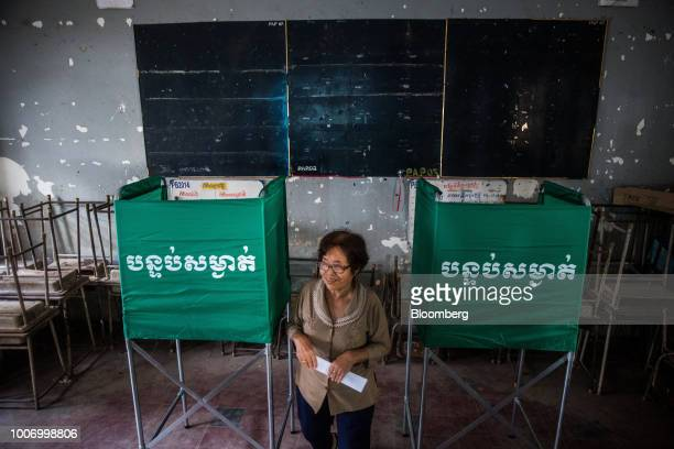 A voter walks past booths after marking her ballot for the general election at a polling station in Phnom Penh Cambodia on Sunday July 29 2018 As...