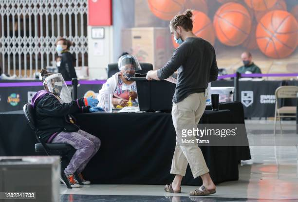 Voter walks toward an election official who is wearing a face shield, mask and gloves at a Vote Center located at the Staples Center on the first...