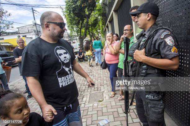 A voter wearing a tshirt with an image of Brazil's rightwing presidential candidate for the Social Liberal Party Jair Bolsonaro arrives at a polling...