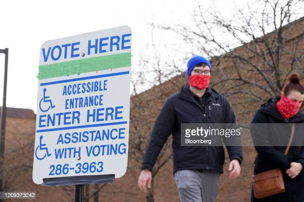 "Voter wearing bandanas walk past a ""Vote Here"" sign outside a polling station in Milwaukee, Wisconsin, U.S., on Tuesday, April 7, 2020. Wisconsin..."