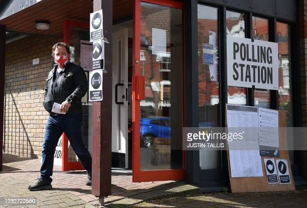Voter wears a facemask with the colours of the Union flag as he exits a polling station in London to cast his vote in local elections on May 6, 2021....