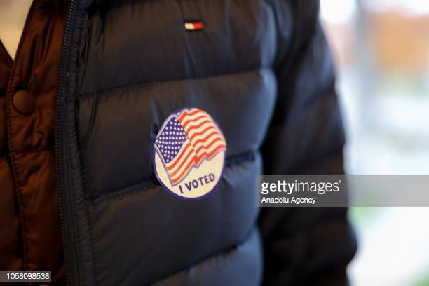 """Voter wears a US Flag badge reading """"I Voted"""" at the polls on early Tuesday to cast their votes in the midterm elections in Fairfax, Virginia, United..."""