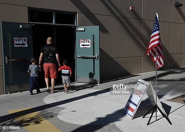 A voter with two children enters a polling station at Ethel WinternheimerStaton Elementary School on Election Day on November 8 2016 in Las Vegas...