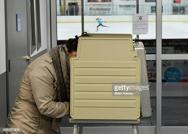 Voter works on her ballot as an ice skater practices at Oakton Ice Arena on November 4, 2014 in Park Ridge, Illinois. Illinois voters are selecting a...