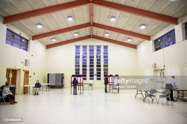 Voters and election officials in the Madison Community Center polling place for the Democratic presidential primary during Super Tuesday on March 3...