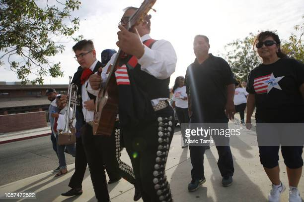Voters and mariachi performers march to a polling place to participate in early voting in California's 25th Congressional district on November 4 2018...