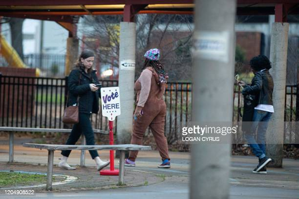 Voters are seen walking in and out of First Ward Creative Arts Academy to cast a ballot during the North Carolina primary on Super Tuesday in...