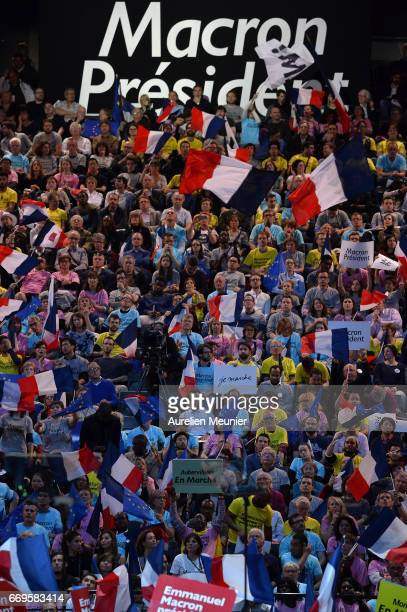 Voters are waving flags as French Presidential Candidate Emmanuel Macron addresses voters during a political meeting on April 17 2017 in Paris France...