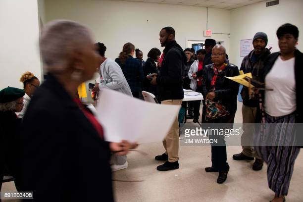 Voters arrive at a polling station to vote after standing in a long line that leads out the doors of the Beulah Baptist Church polling station in...