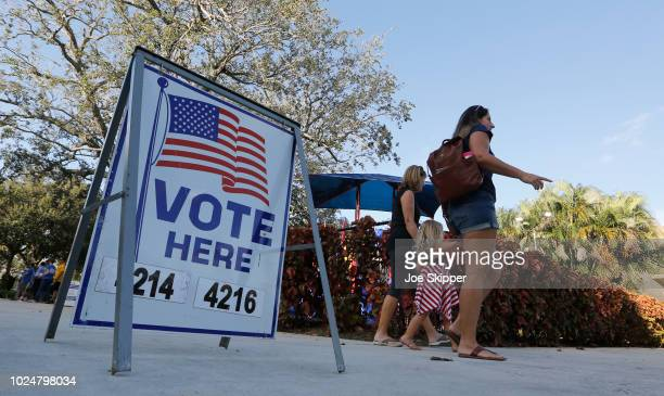 Voters arrive to cast ballots at a polling place on August 28 2018 in Boca Raton Florida Republican Gov Rick Scott is vacating his post to run for...