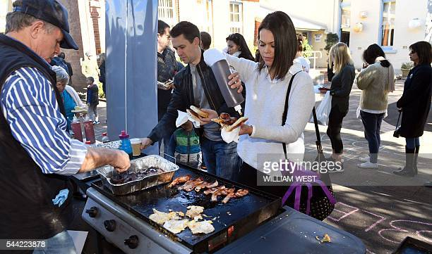 Voters buy sausage sandwiches as they queue at a voting station in the Sydney suburb of Double Bay on July 2 2016 The Australian election is on a...