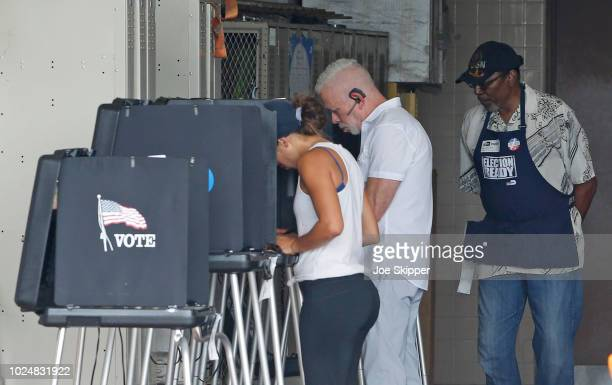 Voters cast ballots as an elections official looks on August 28 2018 in Miami United States The state of Florida has primary day elections as voters...