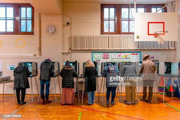 TOPSHOT Voters cast ballots at a polling station in Minneapolis Minnesota on November 6 2018 Americans started voting Tuesday in critical midterm...