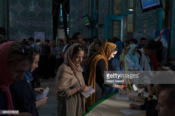 Voters cast their ballots at a polling station for the presidential election on May 19 2017 in Tehran Iran Millions of Iranians voted late into the...