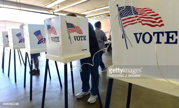 Voters cast their ballots at a polling station in Alhambra California on November 4 2014 Months of campaign promises partisan charges and a seemingly...