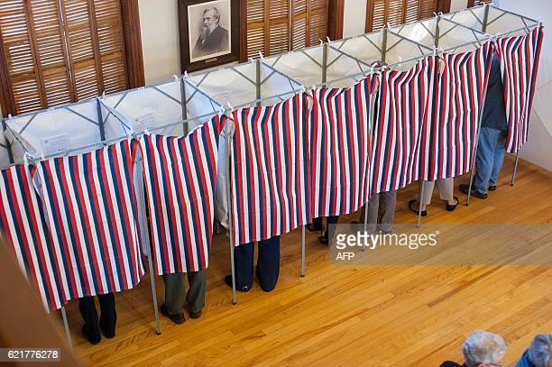 Voters cast their ballots at the Sutton town hall in the US presidential election November 8, 2016 in Sutton, New Hampshire. Eager voters crowded...