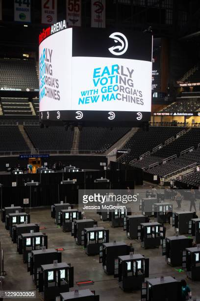 Voters cast their ballots inside of State Farm Arena, Georgia's largest early voting location, for the first day of early voting in the general...