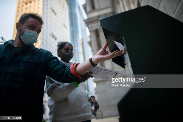 Voters cast their early voting ballot at drop box outside of City Hall on October 17, 2020 in Philadelphia, Pennsylvania. With the election only a...