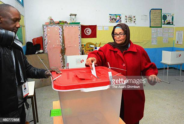 A voters casts a ballot at a polling station on December 21 2014 in Tunis Tunisia The country's first democratic election after the 2011 overthrow of...