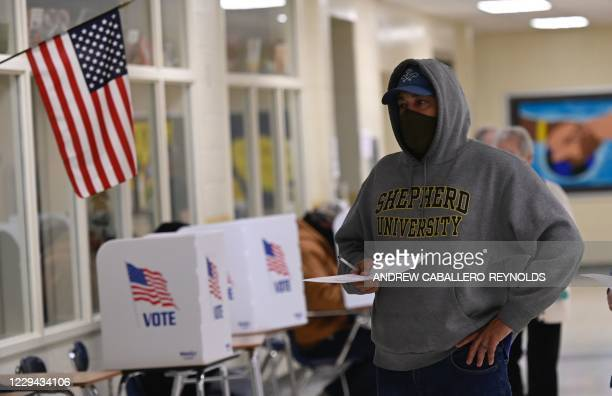 Voters casts his ballot at a polling station on US Election Day in Winchester, Virginia early November 3, 2020. - Polling stations opened in New...