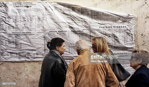 Voters check for the names in the Greek general election at a polling station in a school on January 25 2015 in Athens Greece According to the latest...