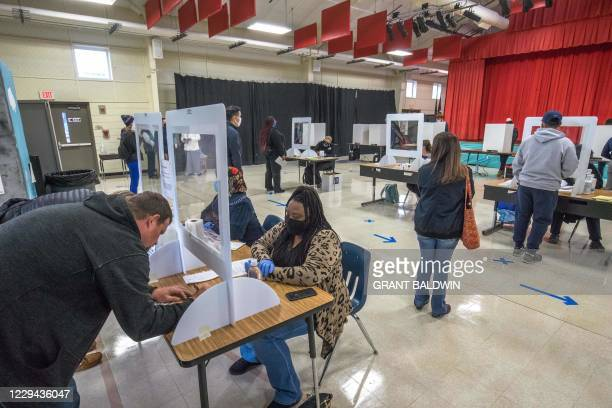 Voters check in at First Ward Elementary School in Charlotte, North Carolina shortly after the polls opened on November 3, 2020. - The United States...
