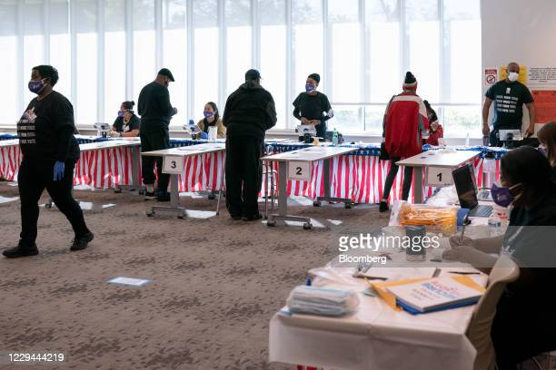 Voters check in with poll workers at a polling location for the 2020 Presidential election in Atlanta, Georgia, U.S., on Tuesday, Nov. 3, 2020....