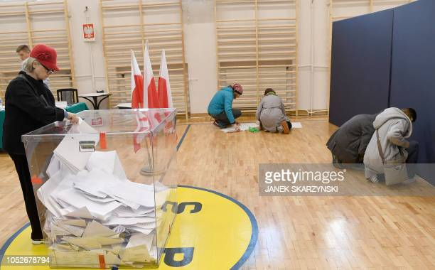 Voters check lists at a polling station during the first round of the local elections on October 21 2018 in the Polish capital Warsaw Poles vote for...