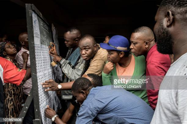 TOPSHOT Voters check the roll at the Monsignor Moke school complex in Victoire district in Kinshasa on December 30 2018 during the DR Congo's general...