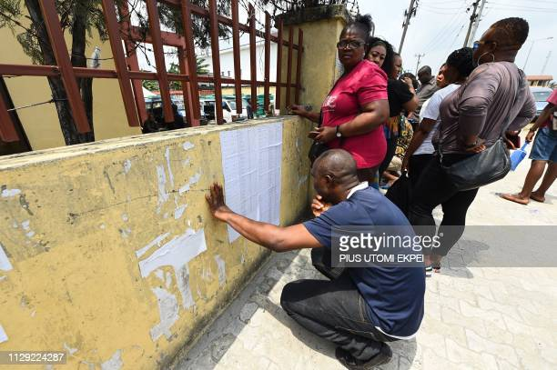 Voters check their names on a voters' list displayed at the Independent National Electoral Commission central office in Port Harcourt Rivers State on...