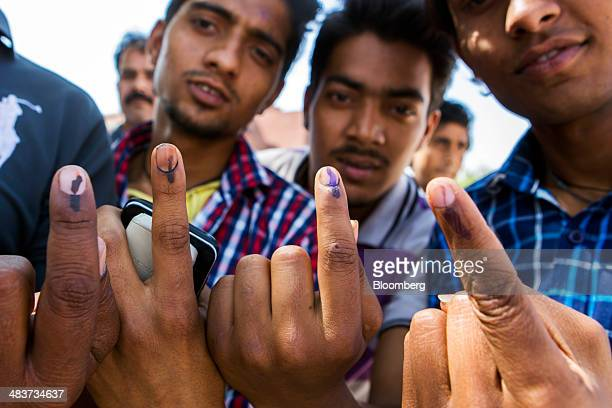 Voters displays their inked fingers for a photograph after casting their votes at a polling station during the third phase of voting for national...